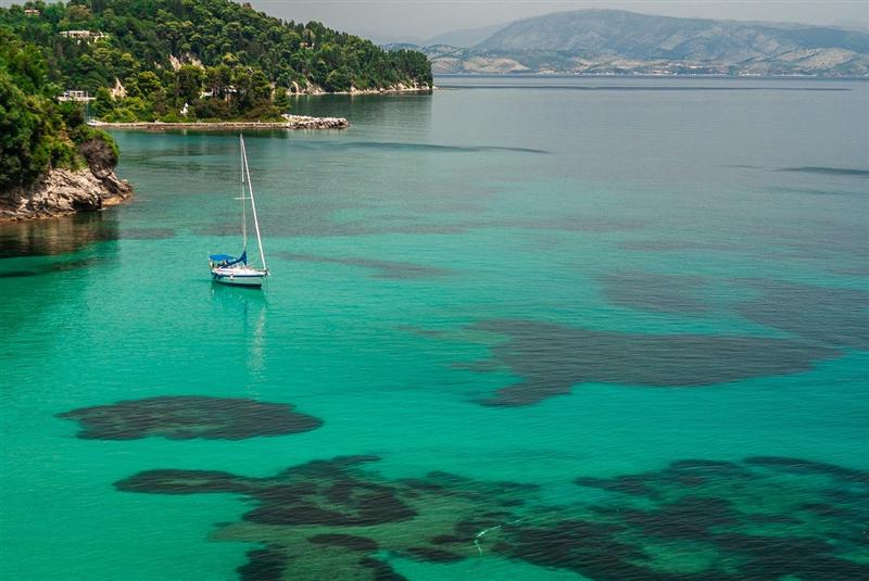 Ambarcatiune navigand pe o mare de culoarea smaraldului in Corfu, Grecia